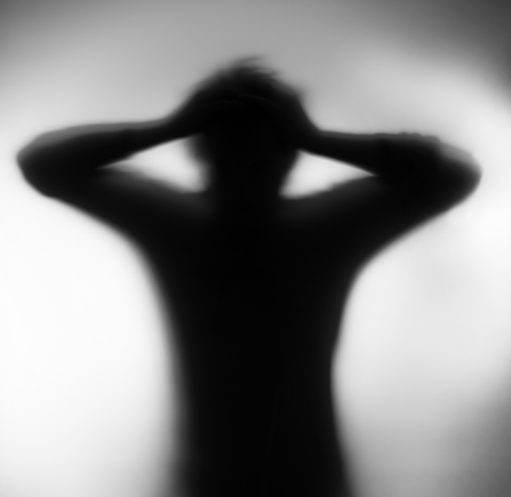 Silhouette of a man holding his head.