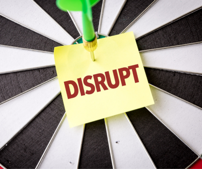 dart going through a post it with the word disrupt on it.