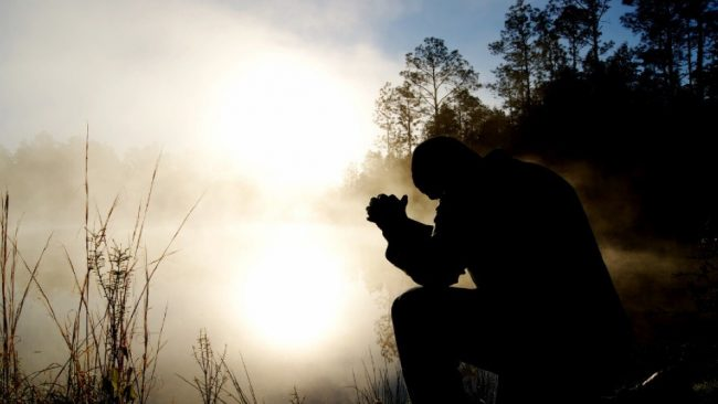 Silhouette praying near a lake.